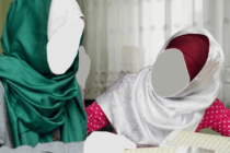 Twee basisschool meisjes met het hoofddoek, gezamenlijk Koran aan het lezen.